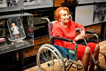Veronica Phillips at the Johannesburg Holocaust and Genocide Centre's permanent exhibition. To the lefs is her childhood doll, kept by her mother in the ghetto of Budapest while Veronica was deported to the camps.