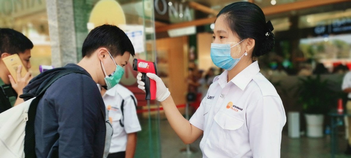 Funcionários verificam a temperatura dos clientes na entrada de shopping center em Yangon, em Mianmar.