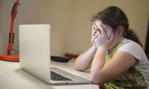 Una joven sentada frente a una computadora portátil tapándose la cara con las manos en Podgorica, Montenegro.