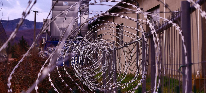 سياج من الأسلاك الشائكة يحيط بمركز احتجاز.