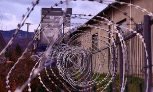 Barbed wire fencing surrounds a detention centre.