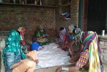 कारोबार गतिविधियों के लिये मोबाइल फोन के ज़रिये ऑनलाइन लेन-देन के गुर सीखती महिलाएँ. इससे उन्हें महामारी के दौरान अपना व्यवसाय जारी रखने में मदद मिल रही है.