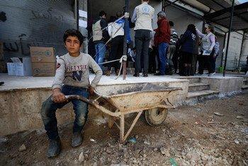 طفل ينتظر أمام مركز توزيع تابع لبرنامج الأغذية العالمي في قرية سنجار جنوب ريف إدلب في سوريا.