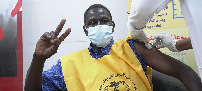 Un trabajador sanitario sudanés haciendo el signo de la victoria mientras se vacuna contra el COVID-19.