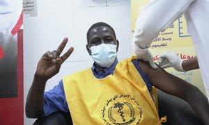 أحد العاملين في مجال الرعاية الصحية في السودان يرفع علامة النصر أثناء تلقيه لقاح كوفيد-19.