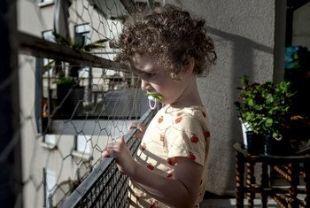 A three-year-old child looks outside their home in Lyon, France, during a lockdown due to the coronavirus pandemic.