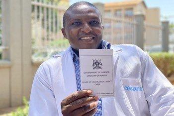 Mfanyakazi wa afya nchini Uganda Dkt. Ombeva Malande akionesha kadi yake ya chanjo baada ya kupatiwa chanjo dhidi ya COVID-19 katika hospitali ya Mulago jijini Kampala.