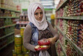 نور (22 عاما) لاجئة سورية تعيش في تركيا، تشتري الطعام في أحد المحلات التجارية باستخدام قسيمة المساعدات النقدية التي يقدمها برنامج الأغذية العالمي.
