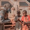 A peacekeeper with MINUSCA, the UN mission in the Central African Republic, explains to two young boys how to properly apply hand sanitizer as protection against coronavirus.