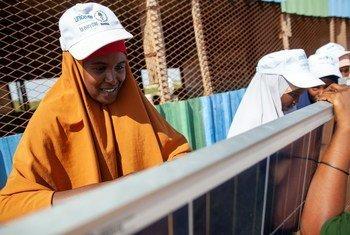 Amina Mahdi Abdi, akijifunza jinsi ya kuunganisha na kufunga mitambo ya umeme inayotumia sola katika kituo kinachopata msaada wa UNICEF huko Dollow nchini Somalia.