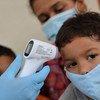 Un médecin prend la température d'une famille de rapatriés en quarantaine dans un abri temporaire au Venezuela.