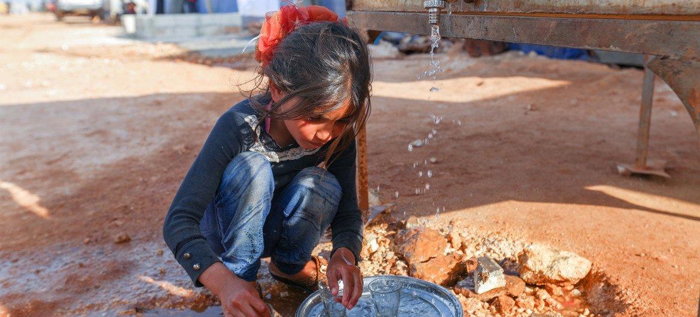 叙利亚伊德利卜的一处流离失所者营地内,一个女孩正在公用水站清洗碗碟。