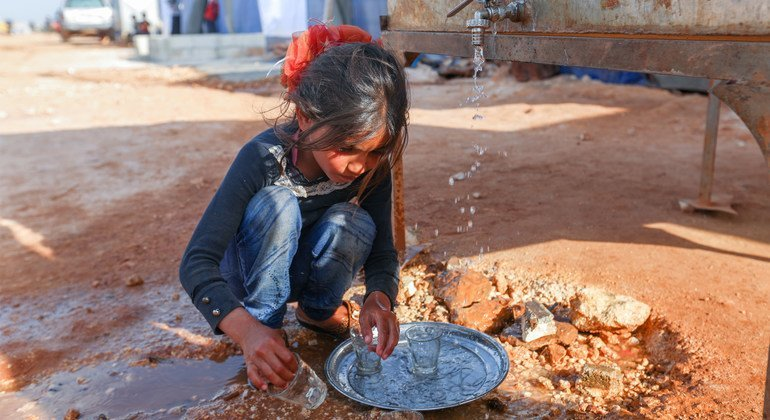 On 23 April 2020, a child washes dishes in the Maarat Misrin camp north of Idlib, Syrian Arab Republic.
