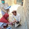 In Afghanistan, a father cradles his child as female health workers administer polio vaccines.