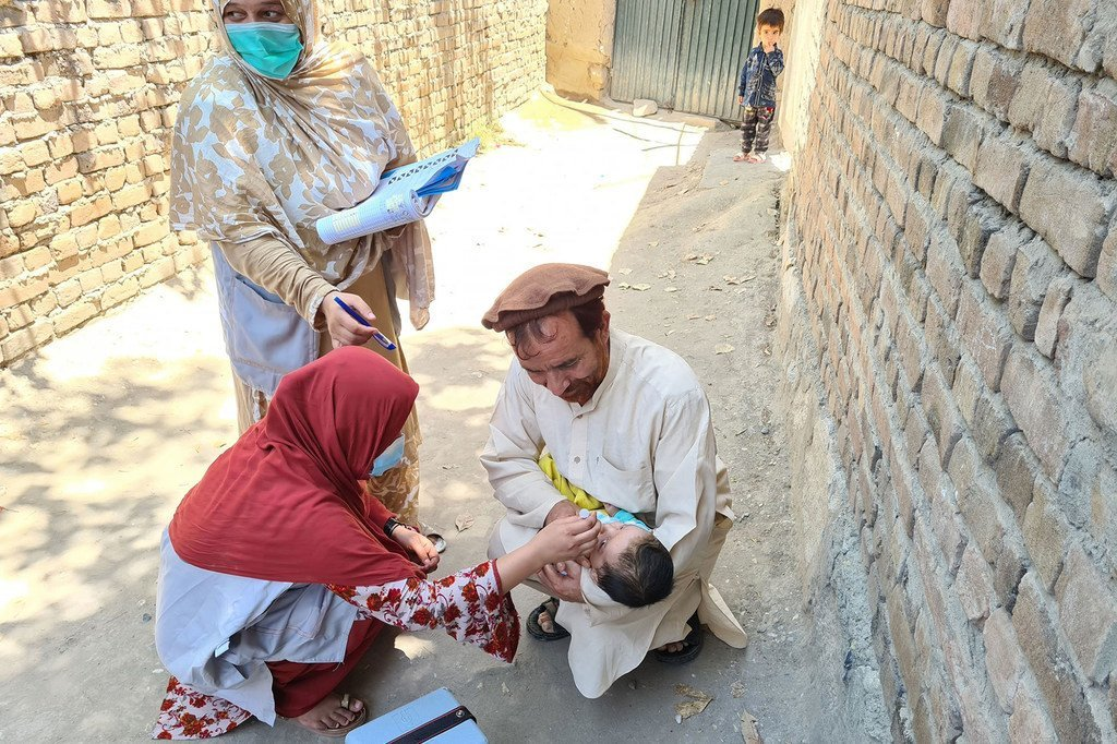 Nchini Afghanistan, baba akisaidia kakimbembeleza mtoto wake wakati muhudumu wa afya akimpatia chanjo ya polio.