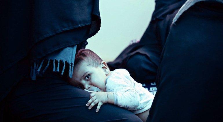 Las mujeres y los niños que viven en zonas de conflicto, como esta madre y su hijo refugiados en un campamento en Siria, sufren especialmente la falta de acceso a sistemas de salud seguros.