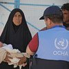 OCHA staff assist an Iraqi woman taking her four-day-old grandson to a health clinic in Al Hol camp, Syria. (16 June 2019)