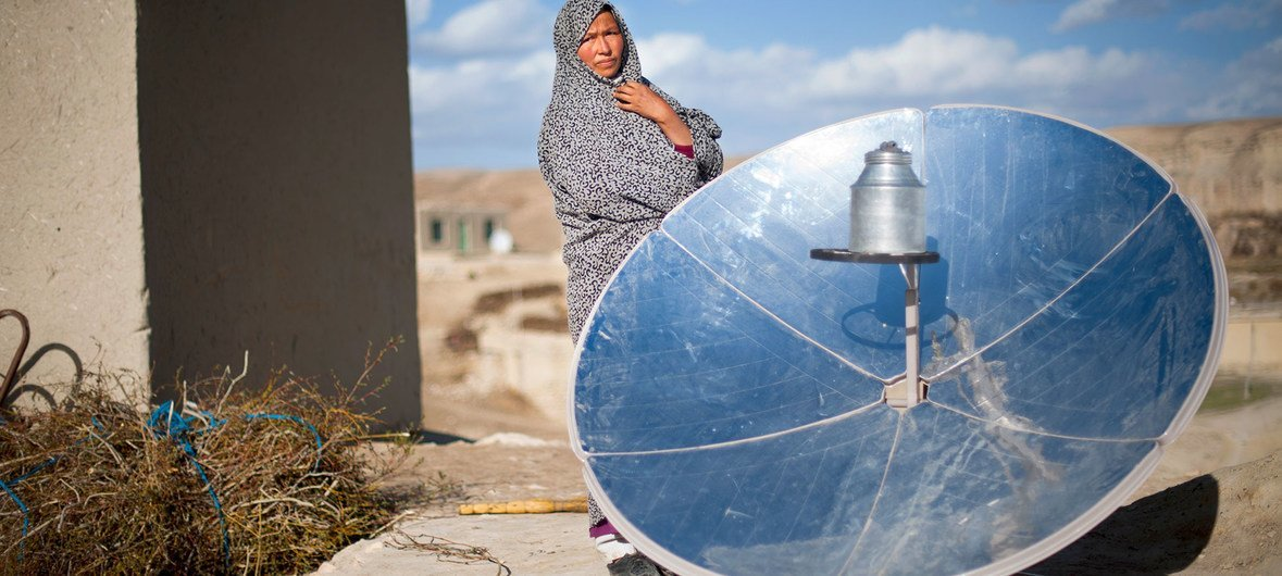 A woman in Afghanistan stands next to a solar cooking disc. (31 May 2015)