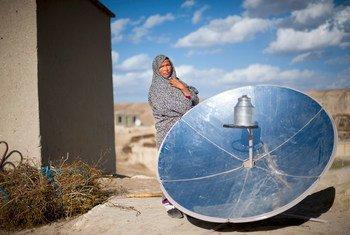 Mulher no Afeganistão junto a antena de energia solar