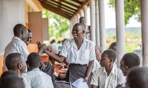 A schoolgirl in Uganda interacts with classmates.