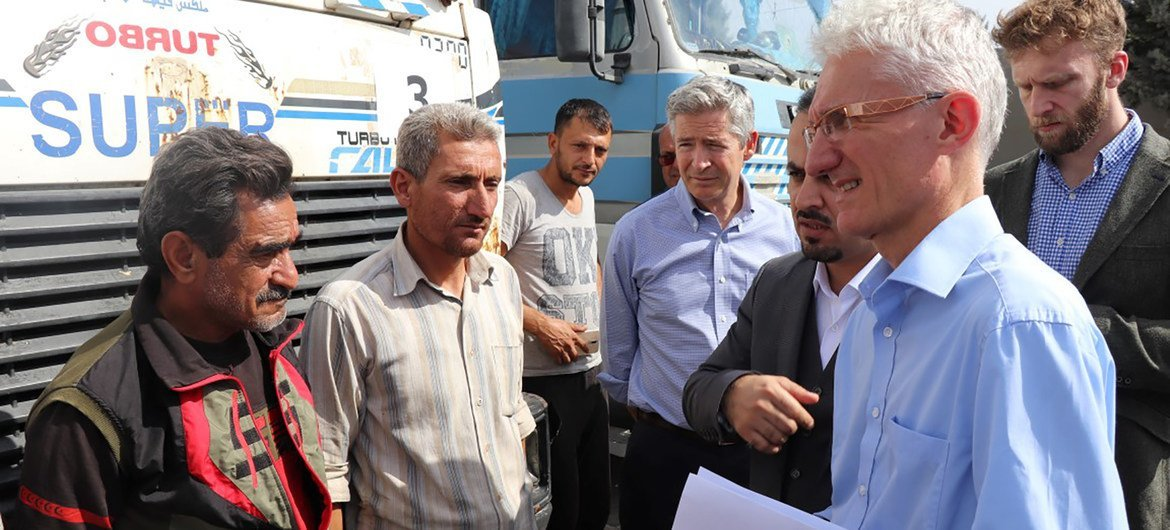 The UN Humanitarian Coordinator, Mark Lowcock (r), meets with a group of Syrian drivers on the Turkish side of the two countries' common border (file photo).