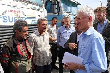 联合国人道主义协调员马克·洛科克(右)在土叙两国边界的土耳其一侧会见一群叙利亚司机。