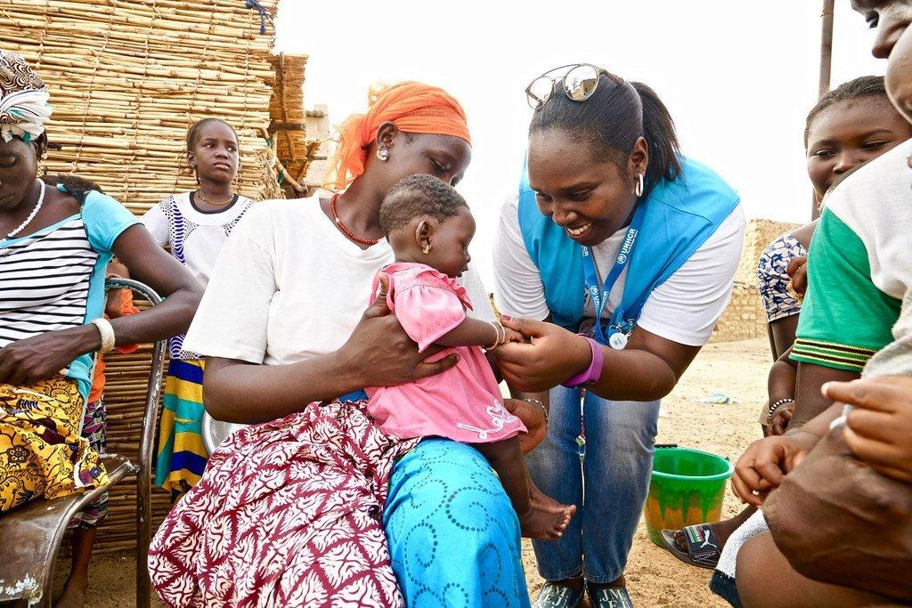Un travailleur humanitaire de l'Agence des Nations Unies pour les réfugiés (HCR) s'occupe d'un bébé dans un centre de santé soutenu par l'ONU dans la région nord du Burkina Faso.