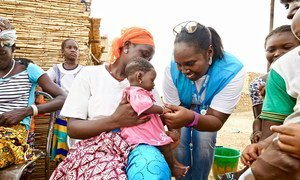 An aid worker from the UN refugee agency attends to a baby at a UN-supported health center in the northern region of Burkina Faso.