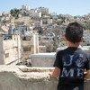 Hamid, de 8 años de edad, se asoma a la vieja ciudad de Hebrón desde el techo de su casa. (12 de julio de 2018).