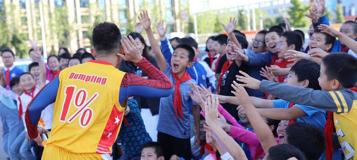 姜山在中国的校园中教授小朋友花式篮球动作。