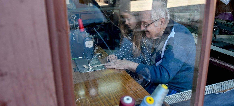 رجل يحيك الملابس، وإلى جانبه حفيدته، في ورشته بمنزل العائلة. جمهورية مقدونيا الشمالية.