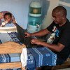 A father takes care of his young child while working from home in Madagascar.