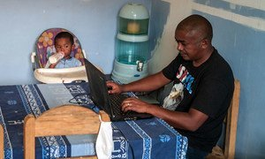 在马达加斯加,一位父亲在家工作的同时照顾着年幼的孩子。