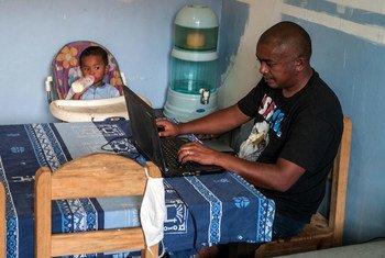 Un hombre cuida a su hijo mientras trabaja desde la casa en Madagascar.
