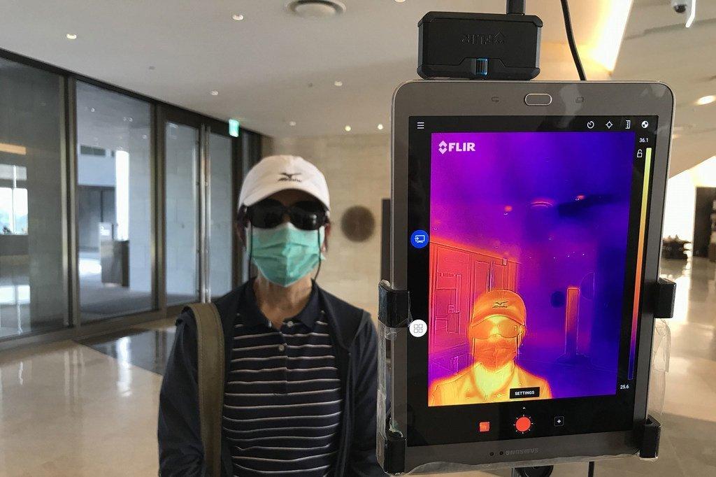 Un thermomètre infrarouge est utilisé pour vérifier la température des clients à l'entrée d'un hôtel à Yangon, au Myanmar.