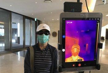 Um termômetro infravermelho é usado para verificar a temperatura dos hóspedes na entrada de um hotel em Yangon, Mianmar.