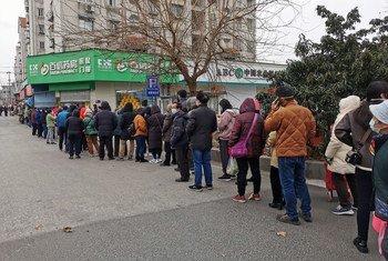 Residentes en la ciudad china de Nanjing hacen cola para comprar mascarillas contra el coronavirus.