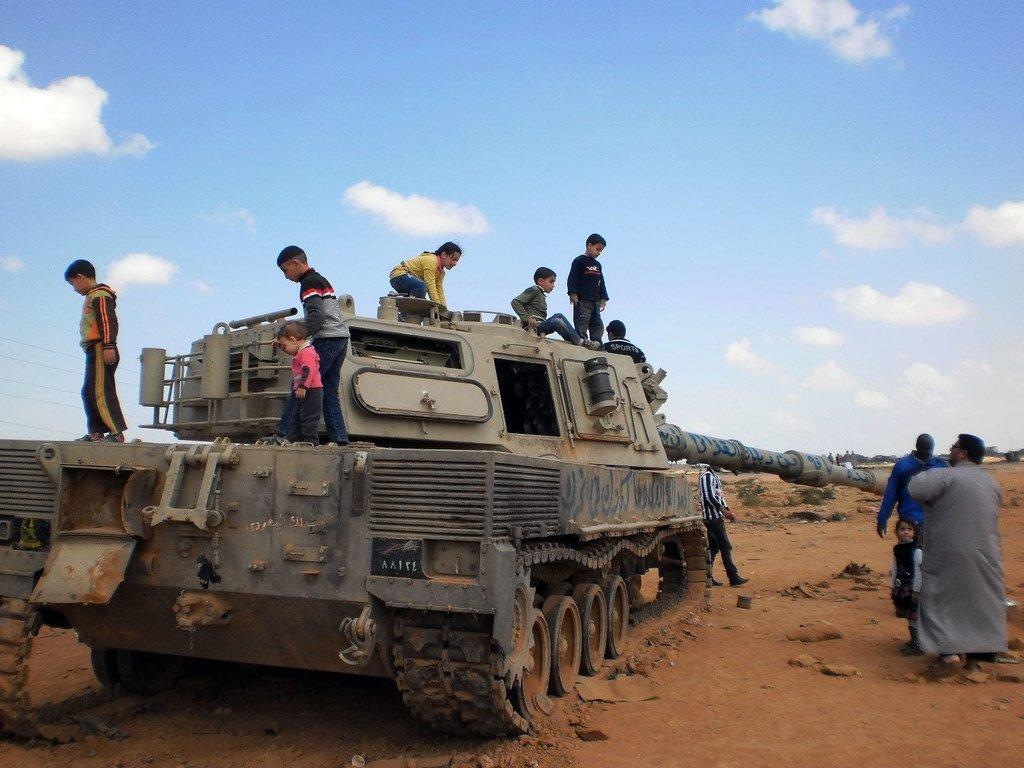 دبابة مدمّرة أصبحت أداة يلعب بها الأطفال في بنغازي بليبيا (آذار/مارس 2011)