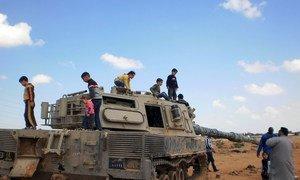 """أطفال يلعبون على ظهر دبابة مدمرة في بنغازي بليبيا - آذار/مارس 2011-  الأمم المتحدة في جنيف (شباط/فبراير 2020) تجع الطرفين اللبيين لإعداد  """"اعداد مسودة اتفاق للوقف الدائم لإطلاق النار وتسهيل العودة الآمنة للمدنيين الى مناطقهم ."""
