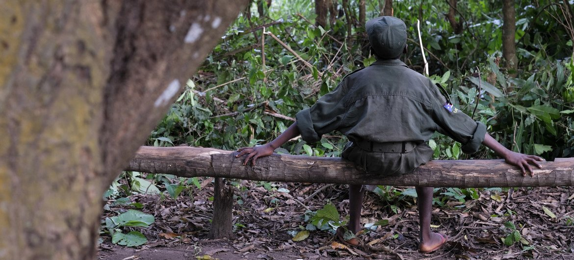 A child solider sits on a log during a ceremony to release children from an armed group in South Sudan, in 2018. However, the risks of recruitment and use of children by armed forces and groups have risen due to the impact of the COVID-19 pandemic.