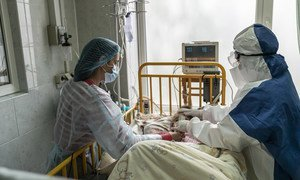 A mother and a doctor tend a girl with COVID-19 at an intensive care ward, in Chernivtsi, Ukraine.