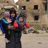 Une mère avec ses deux enfants dans la ville détruite d'Alep, en Syrie.