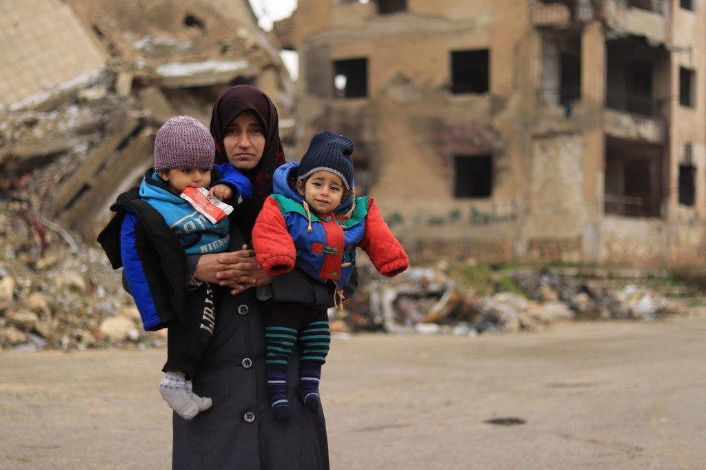 在叙利亚阿勒颇市,一位母亲抱着两个孩子。