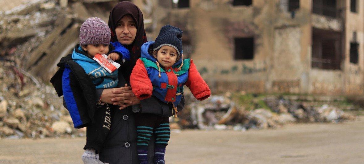 سيّدة تحمل طفليْها في مدينة حلب التي تعرّضت للدمار في سوريا
