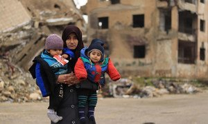 A mother holds her two children in the destroyed city of Aleppo in Syria.