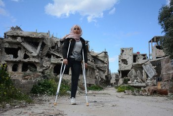 Nour, 16, stands in her war-ravaged and now partially inhabited neighbourhood of Karm Al-zaitoun in Homs city, Syria.