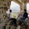 Two children, who recently returned home after they and their family fled fighting in 2017, look out over the Al Gamalia neighborhood of Taiz City.