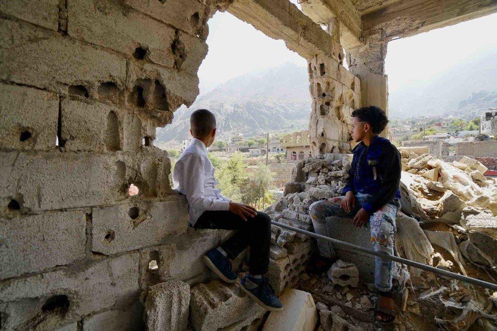 Deux enfants, récemment rentrés chez eux après avoir fui les combats en 2017 avec leurs familles, regardent le quartier Al Gamalia de la ville de Taëz, au Yémen.