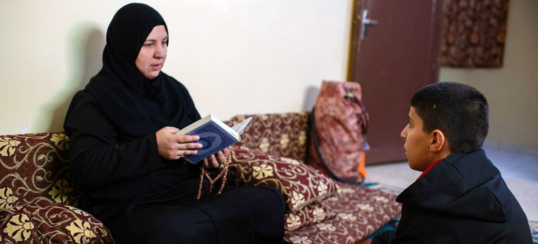 Uma refugiada síria que mora na Jordânia lê o Alcorão com seu filho em sua casa em Amã
