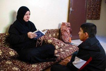 Une réfugiée syrienne vivant en Jordanie lit le Coran avec son fils chez elle, à Amman.